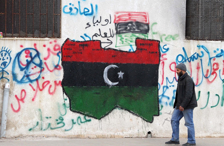 A man walks past graffiti of the flag that has been adopted by the rebel movement in eastern Libya on 16 March 2011.