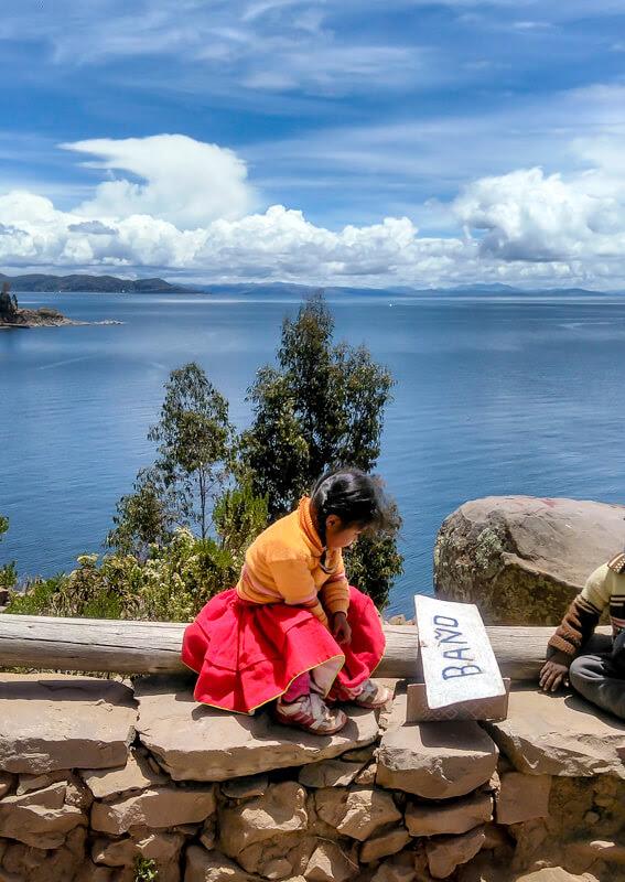 little_peruvian+girl+sitting+taquile+island+puno+lago+titicaca+peru