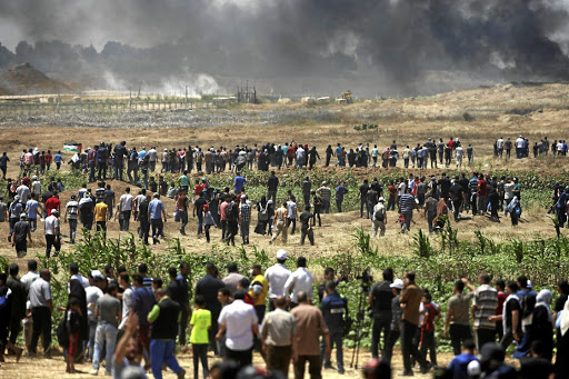 Palestinian demonstrators gather at the Israel-Gaza border during a protest against the US embassy's move to Jerusalem, east of Gaza City, on May 14 2018. Picture: REUTERS