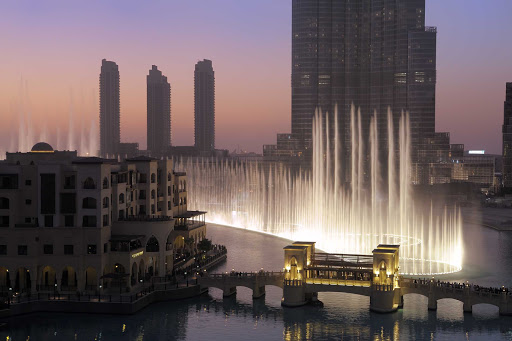 The Dubai Fountain illuminates at twilight on Burj Khalifa Lake, part of downtown Dubai.