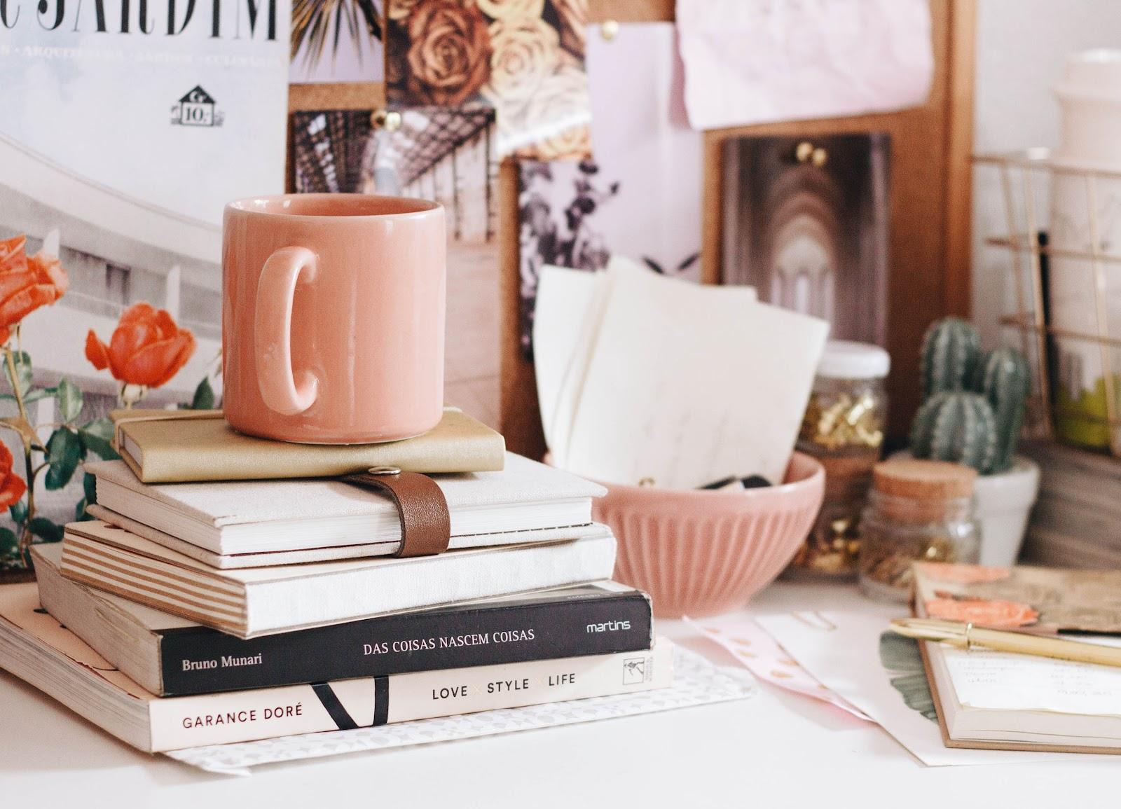 Schreibtisch mit Büchern, Notizbüchern, einer rosafarbenen Tasse und Dekoartikeln im Journaling Ambiente