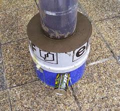 Photo: Le mélange réfractaire est tassé correctement dans le bidon. Le rouleau en plastique permet son extraction facile en le déroulant