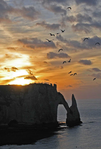 The arch rock and chalk cliffs of d'Etretat are part of the stunning views of Normandy, France.