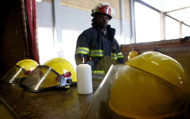 Central fire station commander, Chico Nyathi looks at a candle that is placed next to helmets of three firefighters who lost their lives trying to extinguish a fire at a building in Johannesburg CBD on September 6 2018