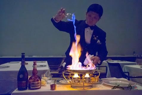 カラメルソースに燃えるブランデーを注ぎ込む
