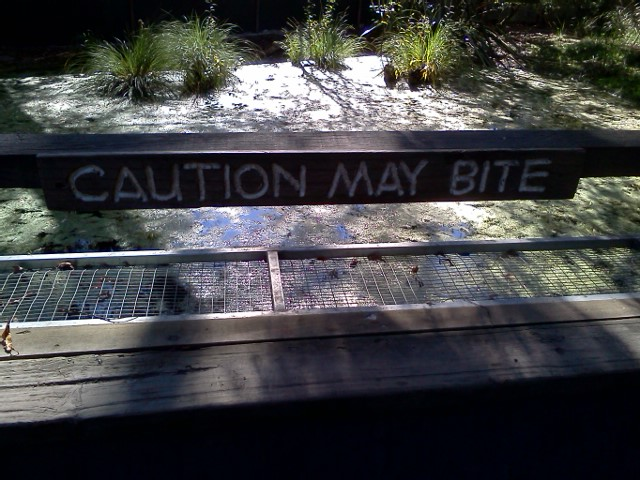 "Photo: Beware, ""Caution May Bite"", sign posted at the Willowbank Wilderness Reserve, NZ"