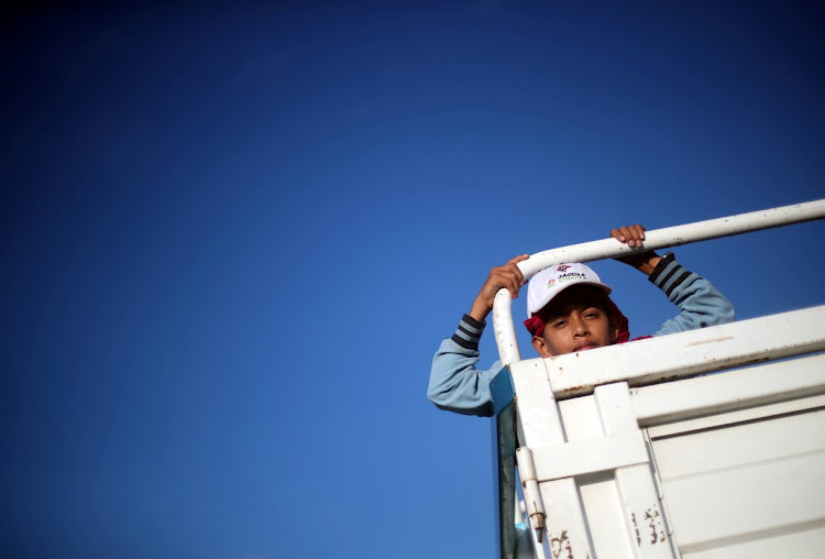 A Central American migrant hitchhikes on a truck along the highway to Santiago Niltepec, Mexico.