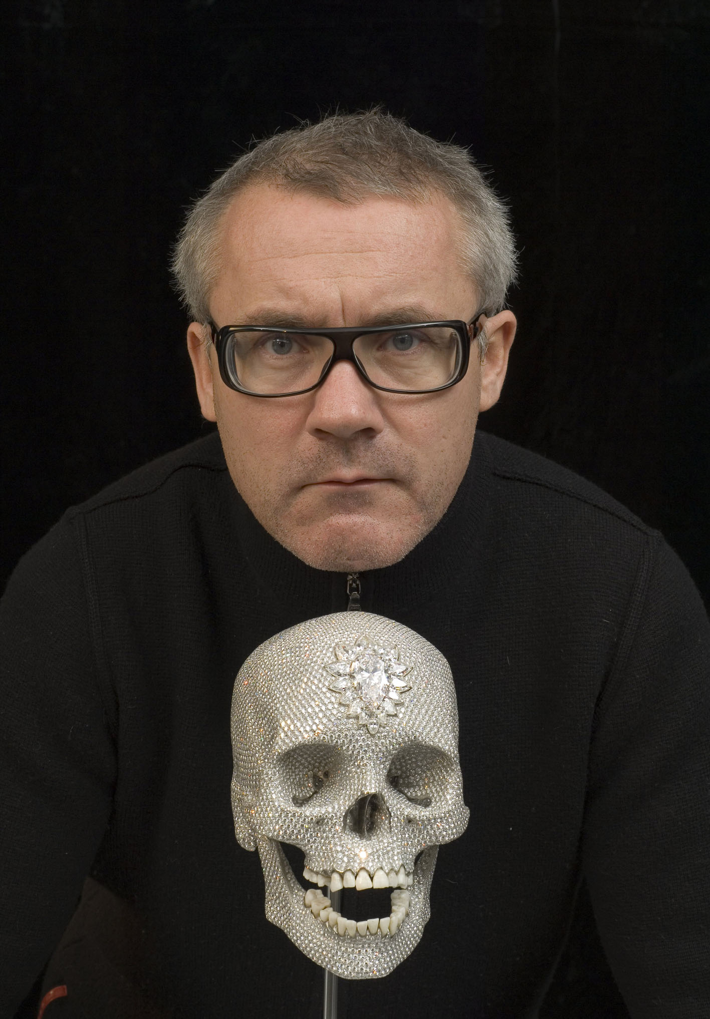British artist Damien Hirst poses with a diamond-encrusted platinum skull, in London