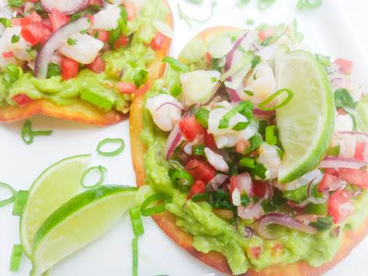 Shrimp Ceviche Tostadas Served On A White Platter With Lime Wedges.