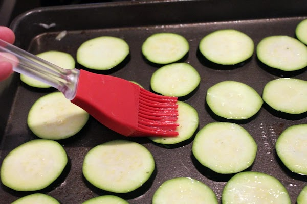 Coating zucchini rounds with egg wash.