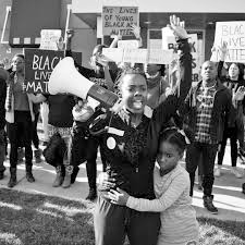 Screen capture/image from the documentary Whose Streets? Two girls at standing in the front, one holding a microphone with her hands up. Behind are protestors holding signs that says BLACK LIVES MATTER.