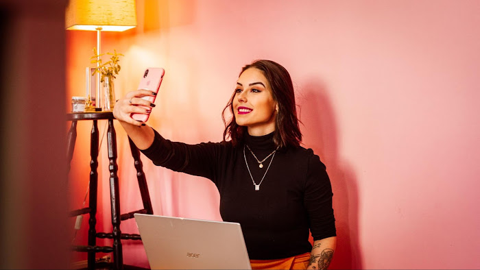 A woman taking a selfie in front of a pink wall.