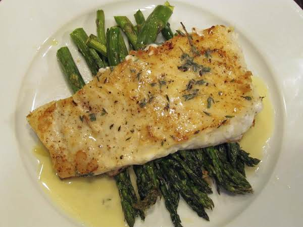 Baked Halibut With Lemon Butter Over Asparagus.