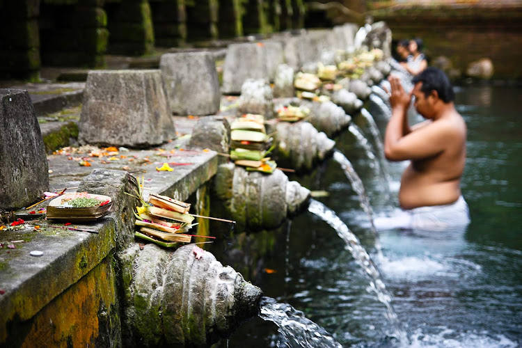 "Jelle Oostrom: ""For more than 1,000 years, Balinese worshipers have been drawn to Pura Tirta Empul, whose sacred spring is said to have been created by Indra and to have curative properties. The tradition continues almost unchanged at the temple today."""