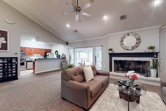 Clubhouse with lounge seating, fireplace, and access to community kitchen