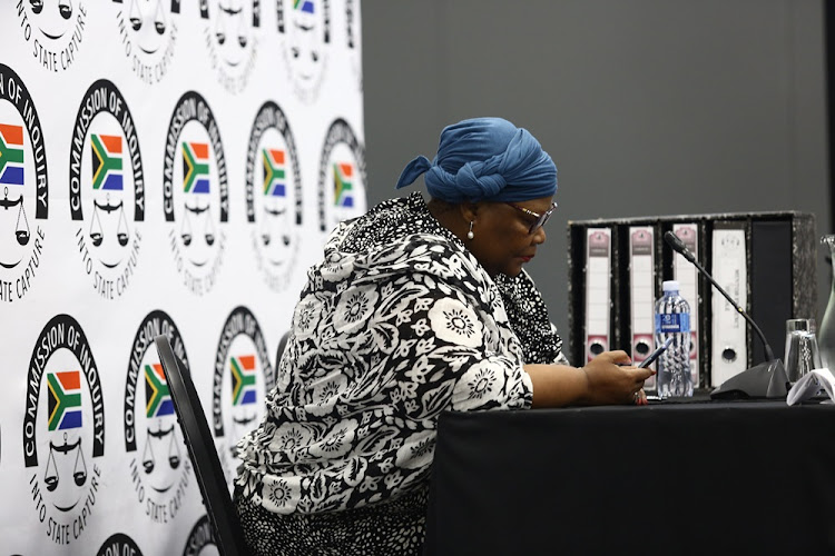 Former ANC MP Vytjie Mentor looks at her phone before the start of her cross-examination at the Zondo commission of inquiry into state capture in Parktown on February 11 2019.