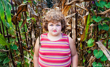 """Photo: The Heart of the Cornfield  It was summer, and the soaring heat of West Virginia was adding to my agitation as I held my Canon 5DMII with my clammy hand. I had spent 4 hours photographing a family I found driving around in Appalachia – and I still hadn't got a single magic shot. Right when I was going to give up, I saw through the family's fence this girl playing in the cornfield. I took to my heels and ran next door. At first, her mom wasn't interested, but after much persistent begging, she consented to """"one"""" photograph. And that one photograph was magic."""