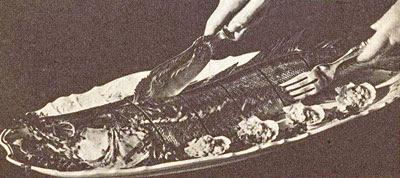 Photo: Roston sült vagy egészben főtt hal egyben tálalva. Az asztalnál felszeletelt halat először a gerincén, majd az oldalún végjük fel, mert a csont és szálkák irányában könnyebben szeletelhető. - Krojenie ryby pieczonej w całości.