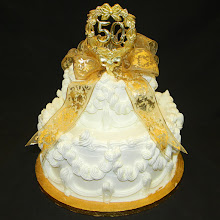 Photo: Lisa's Traditional 2-tier cake with ornate gold metallic French ribbon bow topper & 50th Anniversary piece.