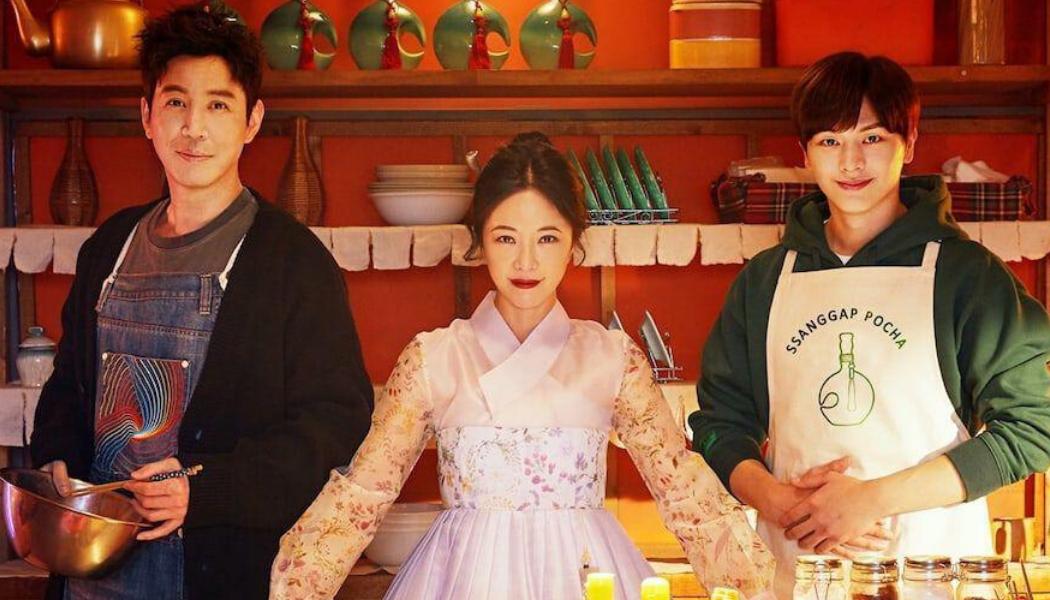 Imagem exibindo três protagonistas em uma cozinha: uma mulher ao centro, com roupas típicas, e dois homens, um de cada lado, trajando aventais.