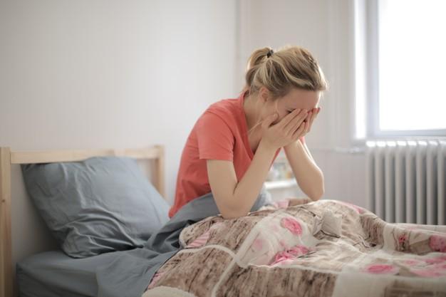 Imagem superficial de uma mulher chorando deitada na cama Foto gratuita
