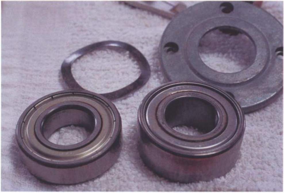 Shown here are outboard (left) and inboard (right) bearings with a wavy washer, which takes up play. The inboard bearing is wider because it is a double-row bearing that better takes the increased radial and axial loads at the inboard end of the spindle. By reading the shield numbers (located at the top on both bearings here), you can go to a bearing supplier and obtain replacements.