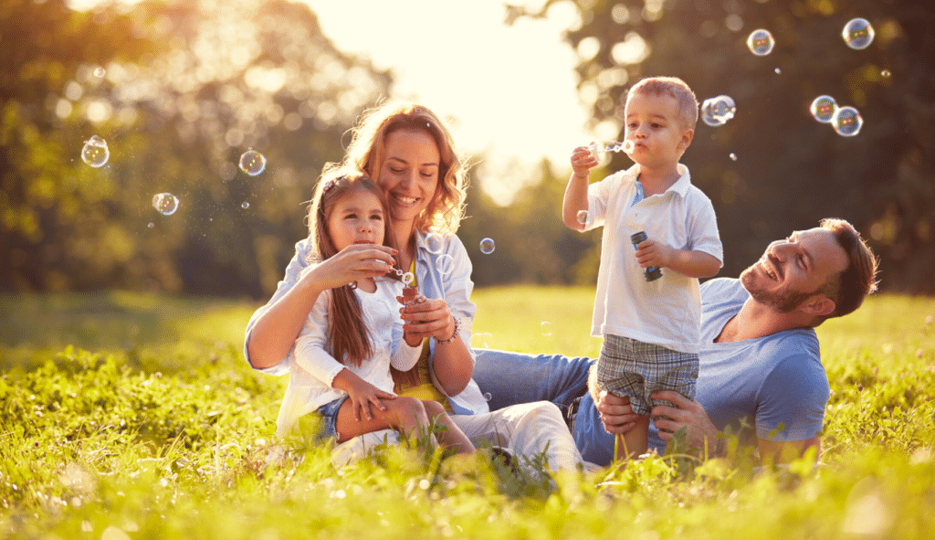 happy family playing in field blowing bubbles