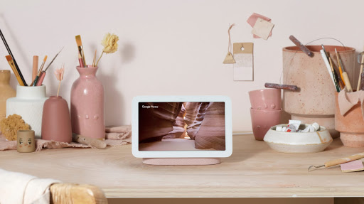 Nest Hub is located on a wooden table displaying pastel colours on screen and surrounded by pottery and tools.