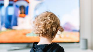 un niño mirando de cerca la pantalla de una televisión
