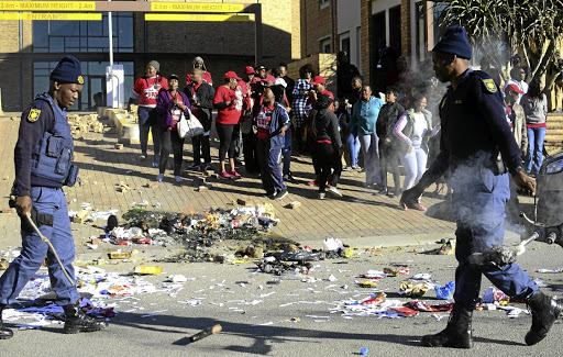 Police clear the road in Mahikeng after angry union members in the department of health blocked it with debris.