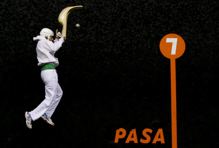 A Jai Alai player jumps high during a match in the Basque country, France.