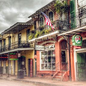 by Laura Prieto - City,  Street & Park  Neighborhoods ( bourbon, new orleans, flag, america, pubs, louisiana, street, american flag, nola, french quarter, bars, mardi gras )
