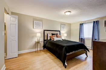 Model bedroom with light wood-inspired flooring, neutral brown walls, and bed with dark comforter