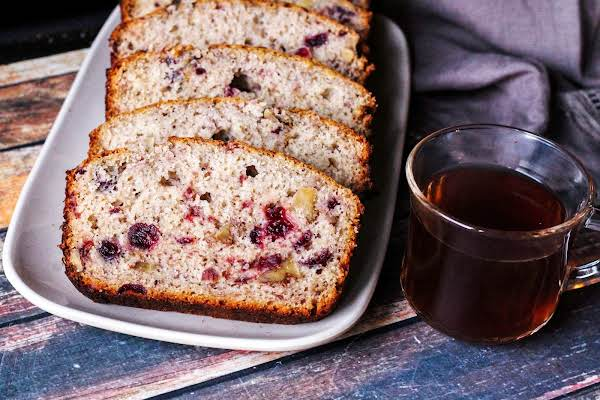 Slices Of Cranberry Banana Tea Loaf Alongside A Cup Of Tea.