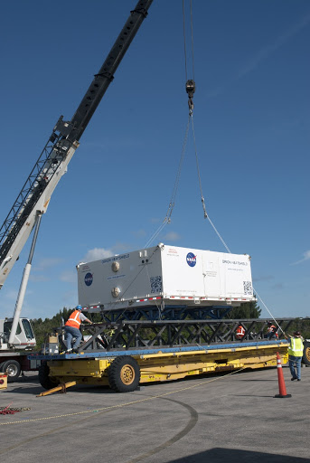 The heat shield for the agency's Orion spacecraft has been offloaded from the Super Guppy aircraft and a crane is loading it on to a transport truck.