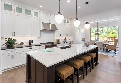 All-white kitchen featuring white cabinets and industrial lighting