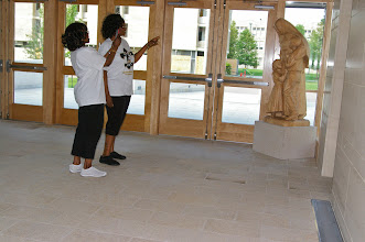 Photo: Associates admire the wood statue of St. Katharine with two children.