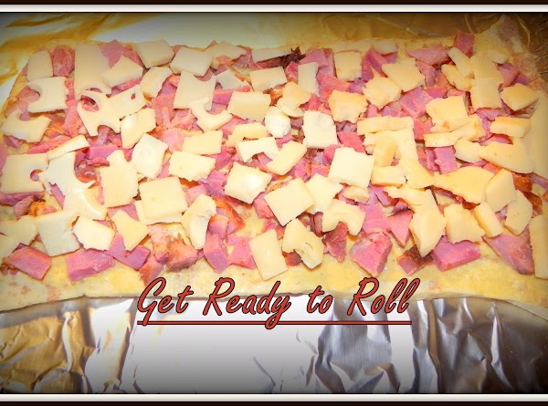 Top with diced/sliced ham and shredded or diced cheese. Carefully reroll dough, starting with...