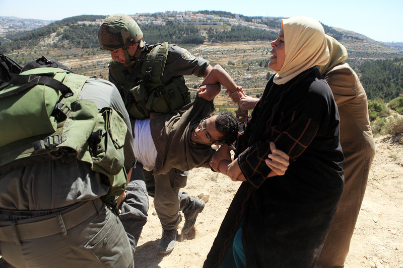 Two Israeli soldiers carry Basil al-Araj as women attempt to stop them