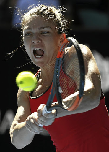 Return to action: Simona Halep returns a backhand to Destanee Aiava in Melbourne on Tuesday. Picture: REUTERS