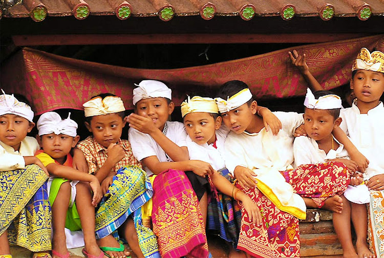 Balinese children watch a ceremony at Pura Panti Timbrah, Paksebali village, Klungkung, Bali.
