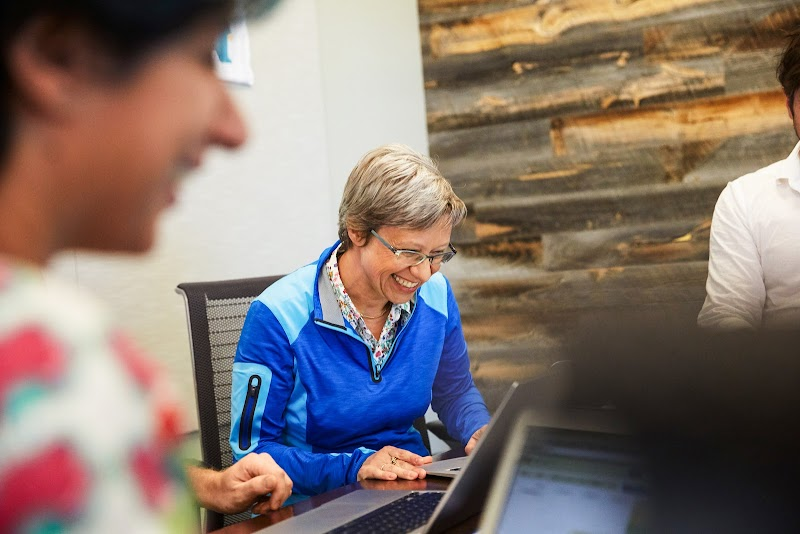 Person with short grey hair in blue shirt smiling at computer.