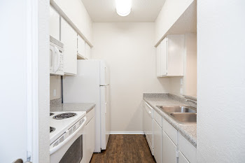 Veranda floorplan's fully-equipped kitchen with wood-style flooring, white cabinets, and white appliances