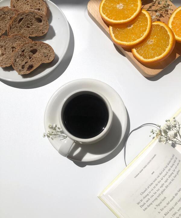 foto de uma xícara de café, pães, rodelas de laranja e um livro
