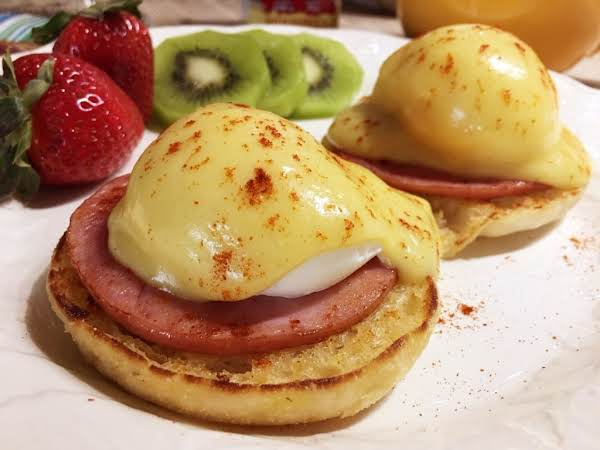 Two Eggs Benedict On A White Plate With Slices Of Kiwi Fruit And Couple Strawberries.