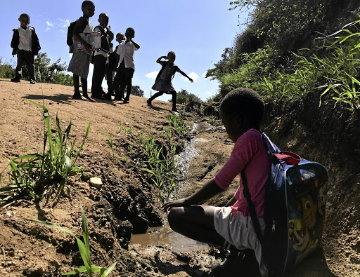 Water crisis: Children play in rain water in Ugu in KwaZulu-Natal, where an intermittent municipal water supply to Murchison Hospital has raised concern about the danger to patients and medical staff. Picture: PHILLIP LENNON