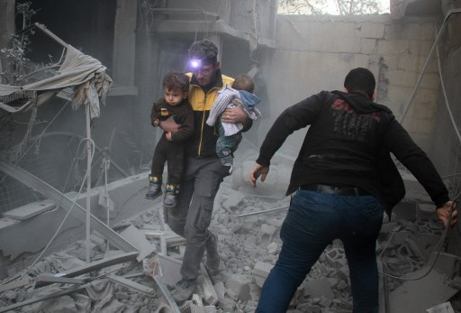 A Syrian man carries two children in the rubble of buildings following regime air strikes on the rebel-held besieged town of Douma in the eastern Ghouta region, on the outskirts of the capital Damascus, on February 7, 2018.