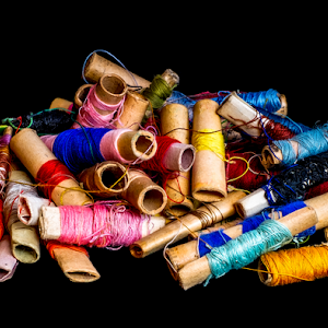 Pile of used colorful spools of thread tailoring, on black background.jpg