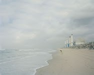 man in beschermend pak onderzoekt strand en water naast een kerncentrale