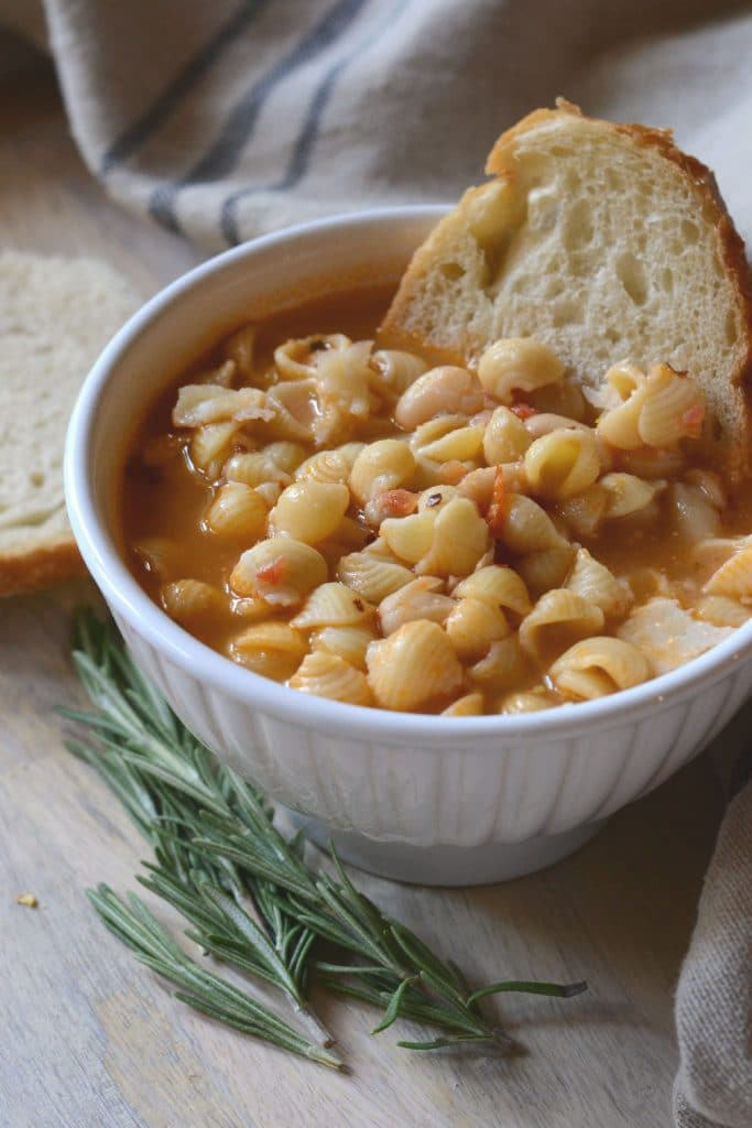 Bowl of pasta e fagioli on a tray with rosemary and crusty bread